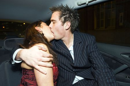 A young couple kissing in tha backseat of a taxi photo