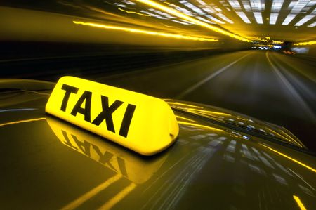 A cab at high speed on a motorway in an urban area with the lit taxi sign on top of its roof Stock Photo - 6492790