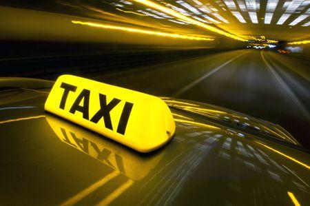 taxi: Una cabina a alta velocidad en una autopista en un �rea urbana con el signo de taxi iluminado por encima de su techo