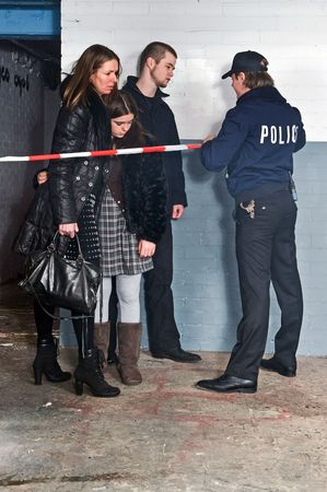 bystanders: Bystanders being kept at a distance by a policeman setting the perimeter of a crime scene with cordon tape Stock Photo
