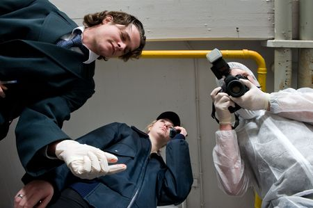 Crime scene investigations team hovering over my dead body. A police inspector, wearing rubber gloves, a policewoman using her radio, and forensic expert taking pictures as evidence photo