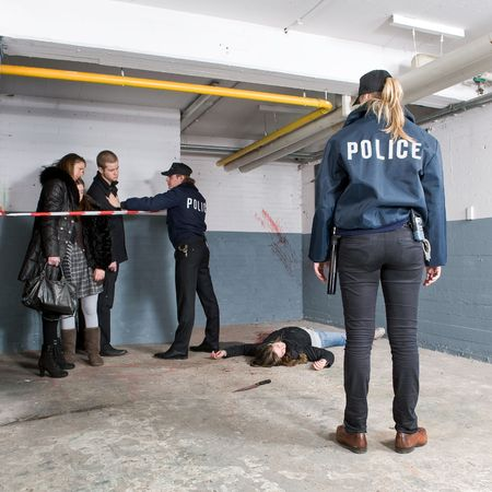 crime scene tape: Bystanders being held at a distance by a police man at a murder scene, with a police woman standing at some distance, looking at the victim Stock Photo