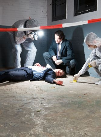 Murder scene with two forensic analysts and a police lieutenant investigating a crime on a businessman in a basement photo