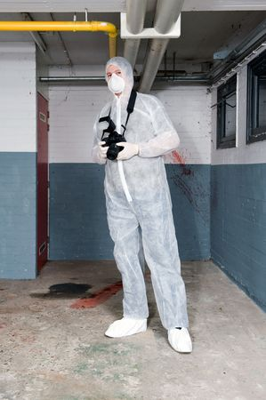 Forensics expert, dressed in a white protective suit, mask and shoe covers, carrying a camera, posing in a basement photo