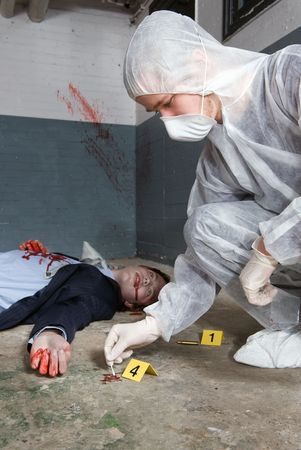 Forensic expert collecting evidence in a crime scene around a dead businessman photo