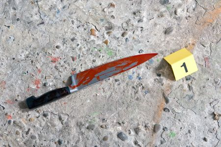 Crime scene photo of a blood covered knife - the murder weapobn - at a crime scene with a placard next to it. photo