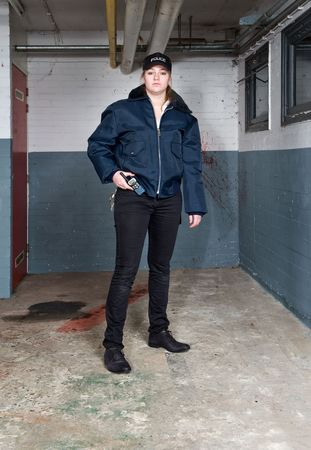 Policewoman looking tough and posing in a basement crime scene photo