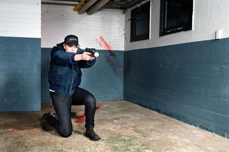sidearm: Police woman aiming her gun and pointing a flashlight in a basement Stock Photo
