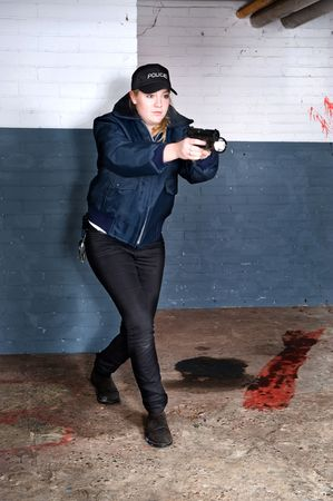 sneaking: Policewoman searching for a suspect, holding her pistol and flashlight up, ready to fire