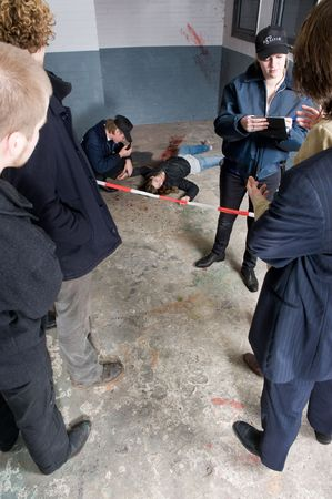 Policewoman interviewing bystanders and witnesses for their statement about a murder having taken place at the crime scene behind her Stock Photo - 6492746