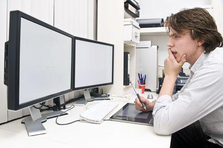 Un giovane uomo al lavoro dietro una stazione di lavoro doppio monitor in un ambiente di ufficio design studio