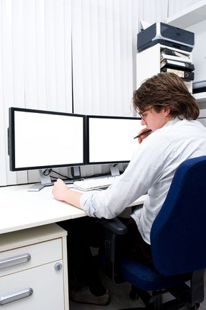 work station: A young designer chewing his pen in thoughts, sitting behind a computer work station.