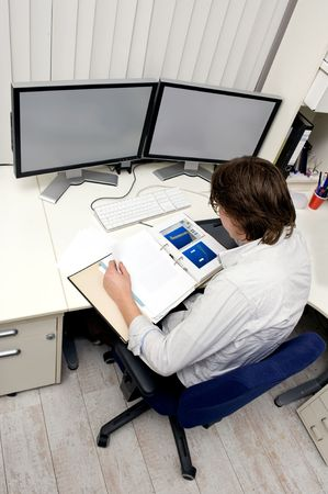 engineering drawing: an engineer studying a thick dossier behind his desk with two computer screens on it Stock Photo