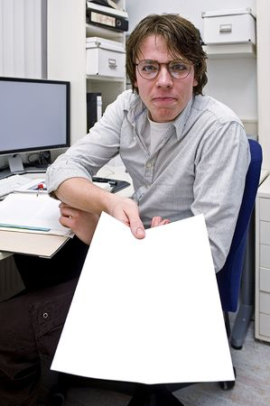 A smug looking young man, showing or handing over a piece of paper with a finalized solution in an office environment photo