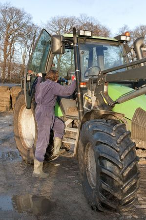 gear handle: Farm hand boarding a big tractor Stock Photo
