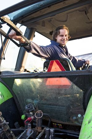Farm hand looking out the rear window of a tractor, hodling the lever Stock Photo - 6552731