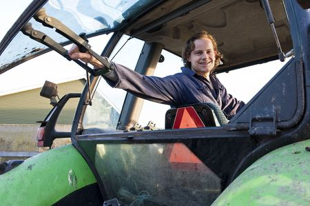 Farm hand looking out the rear window of a tractor, hodling the lever Stock Photo - 6552733