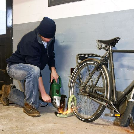 Bicycle thief busy breaking the lock with a portable grinding machine photo