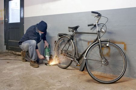 vibrating: Bicycle thief busy breaking the lock with a portable grinding machine