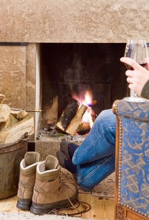 Man relaxing with a glass of red wine by the fireplace after a long hike; his boots off, next to him, warming up Imagens