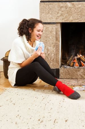 Young woman enjoying a cosy game of cards by the warmth of a fireplace Stock Photo - 6553422