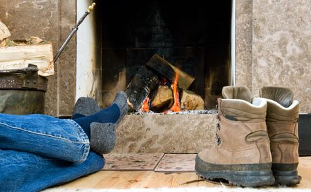 hiking boot: Hiker warming up and relaxing by a small fireplace