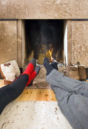 feet crossed: Relaxing by the fireplace - two pairs of feet warming near the fire after a long, cold, winter hike Stock Photo