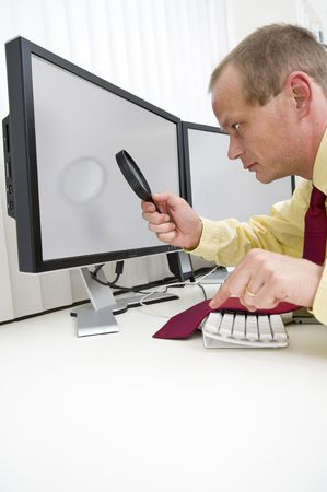 interrupt: Businessman seriously analyzing data on a computer monitor using a magnifying glass, with his left index finger hovering above the escape key to interrupt the process.