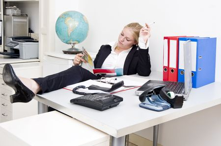 slob: Lazy receptionist, reading a glossy magazine and smoking a cigarette, after having put the phone off the hook Stock Photo