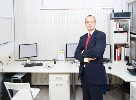 Confident looking business man, posing in front of a well equipped office, representing a small business owner photo