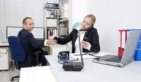 accepting: A businesswoman accepting a third telephone from a colleague, already talking to different people on various lines Stock Photo