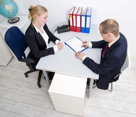 firmando: Empresario firmar un contrato con una empresaria de aspecto evidentemente satisfecho