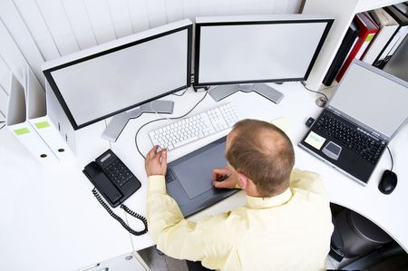 Graphic designer at work behind two big flatscreen monitors and a laptop photo