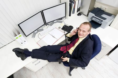 dual: The owner of a small business relaxing behind his desk making several phone calls Stock Photo