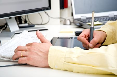The hands of a graphic designer, simultaneously hovering the shift, control, alt and command button, and sliding a stylus over a graphic tablet Stock Photo - 6587294