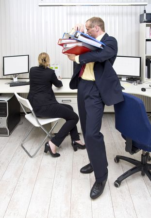 organising: A businessman carrying an armful of dossiers over to his colleague, whos organising her desk
