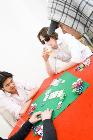 Four people sitting around a table with a red tablecloth for a casual game of poker Stock Photo - 6553528