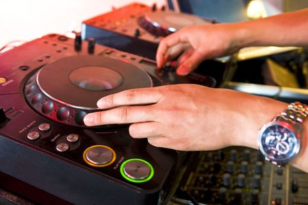 The hands of a dj on a turntable in a club photo