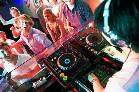 disco parties: Grupo de baile de personas delante de un dj en una discoteca Foto de archivo
