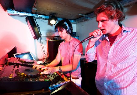 crossfader: A DJ and a mc in action at a party in a nightclub. Stock Photo