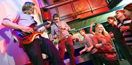 gig: Guitarist and saxophone player, accompanied by a DJ, during a gig with an enthousiastic crowd in a discotheque Stock Photo