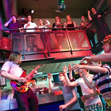 jovenes tomando alcohol: Guitarrista, prerforming vivir en un club nocturno, acompa�ado por un DJ, realizar en un club nocturno Foto de archivo