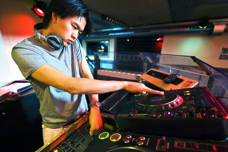 turning table: DJ working on the faders and turntables during his act in a club