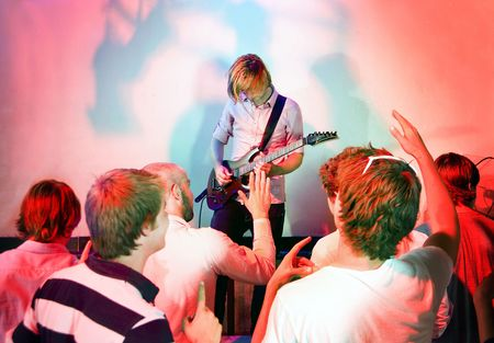 Guitarist, live on stage, in a club with a group of people watching the show photo