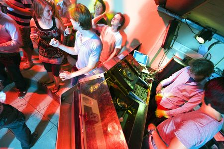 studens: People dancing and flirting near the DJ booth at a nightclub Stock Photo