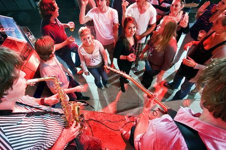 Group of partying people near a stage in a club with two musicians performing Stock Photo - 6598570