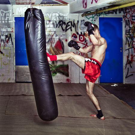 coup de pied: Combattant Muay tha�, donnant un coup de pied avant �nergique durant une pratique rond avec un sac de boxe Banque d'images