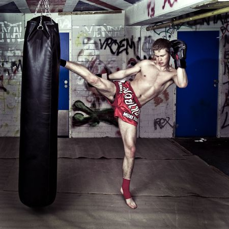bare chest: A muay thai fighter giving a high kick during a practise round with a boxing bag in an urban basement