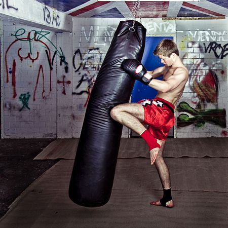 thai kick boxing: Athletic muay thai boxer giving a forceful knee kick during a training with a boxing bag Stock Photo