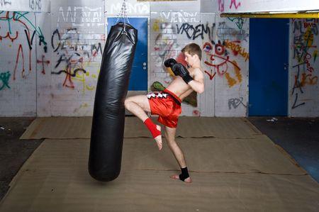 Un muay thai figher donnant un coup de pied au genou lors d'une pratique